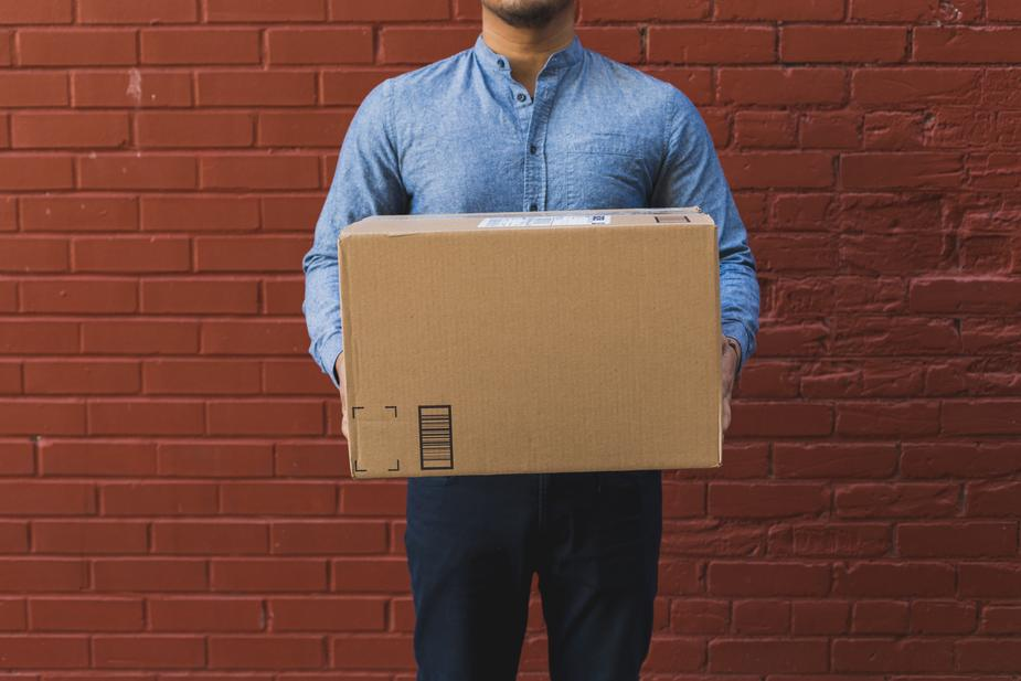 man-holding-shipping-box-on-red-brick